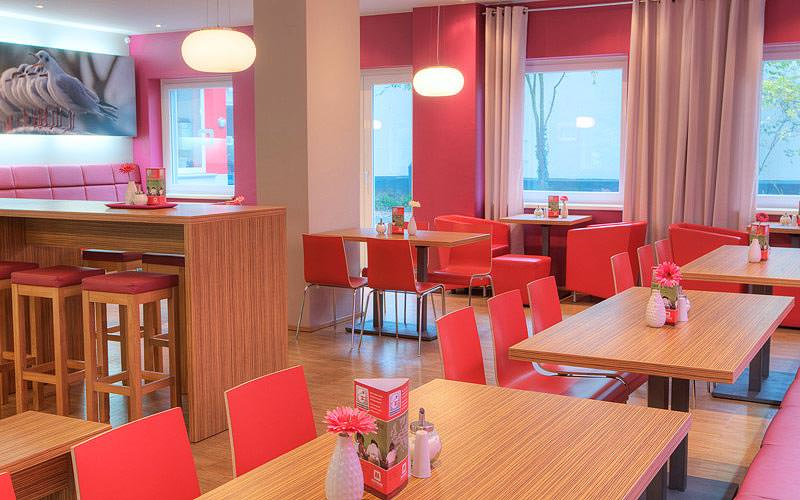 The spacious dining area within Meininger Hotel Hamburg, with wooden tables and red chairs