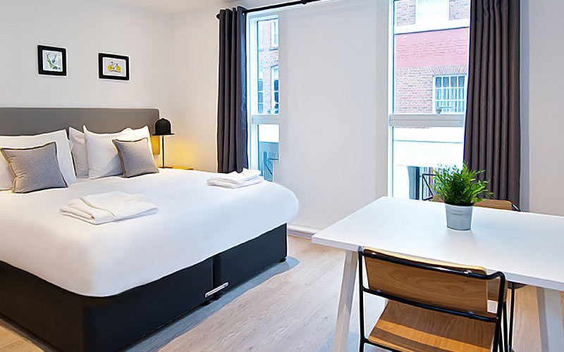 A spacious double room with grey and white bedding, two floor to ceiling windows and a table with two chairs
