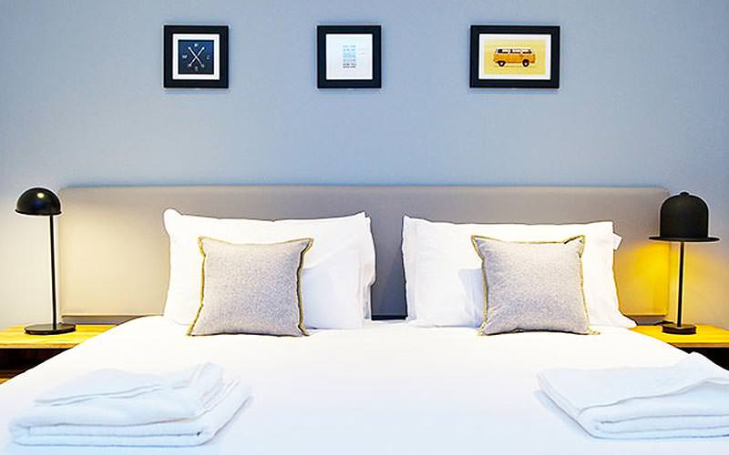 Three small pictures above a large, white bed