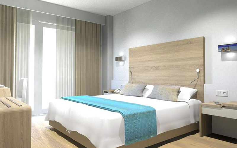 A modern bedroom with a bright blue feature colour on the bed