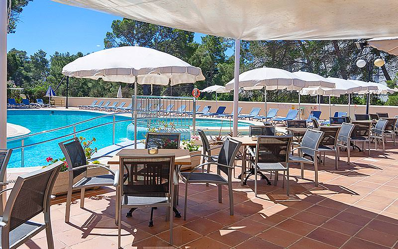 Outdoor seating area at THB Ibiza Mar Apartments with the outdoor pool in the background