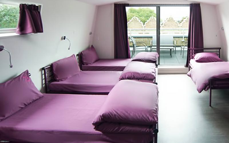 Four single beds with purple bedding in a dorm room, with French doors in the background
