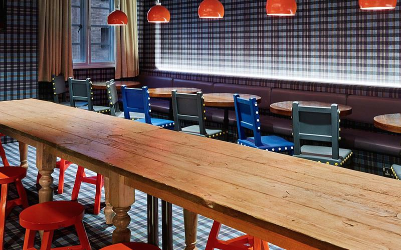 Long wooden tables with red and blue chairs in the restaurant at Generator London