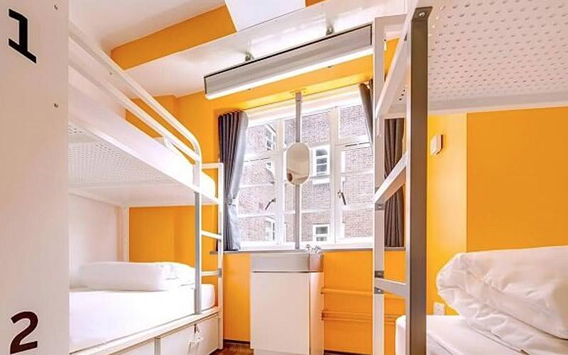 A yellow room with white bunk beds lined against the wall
