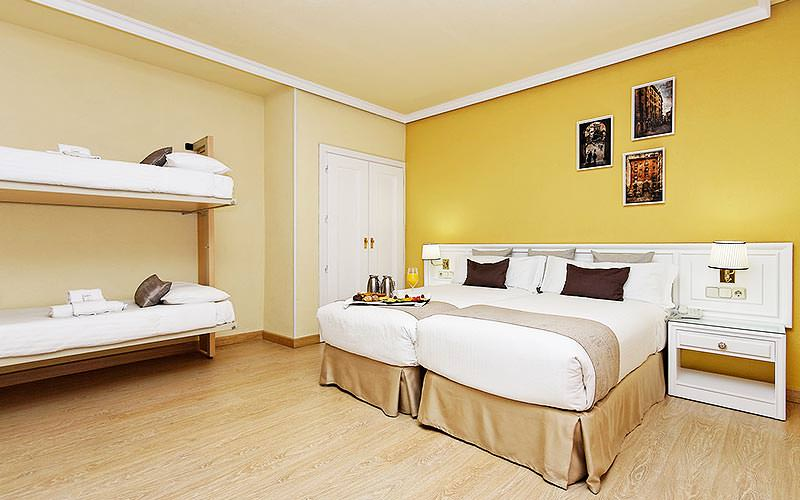 Two beds pushed together with bunk beds on the wall, and yellow and cream walls