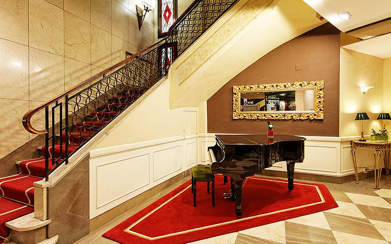 A large staircase with a grand piano at the bottom