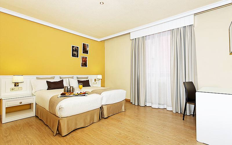 A yellow and cream room with a twin bed and three pictures up on the wall