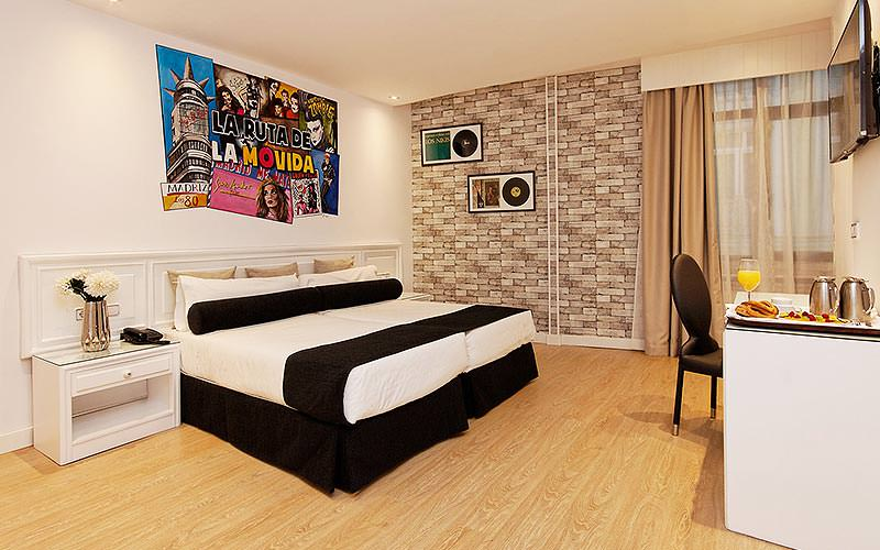 A quirky, modern room with exposed brick work behind the bed and idiosyncratic artwork up on the wall