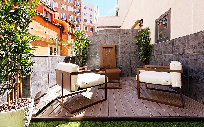 An outdoor terrace with two modern, quirky seats and a rustic table in the middle