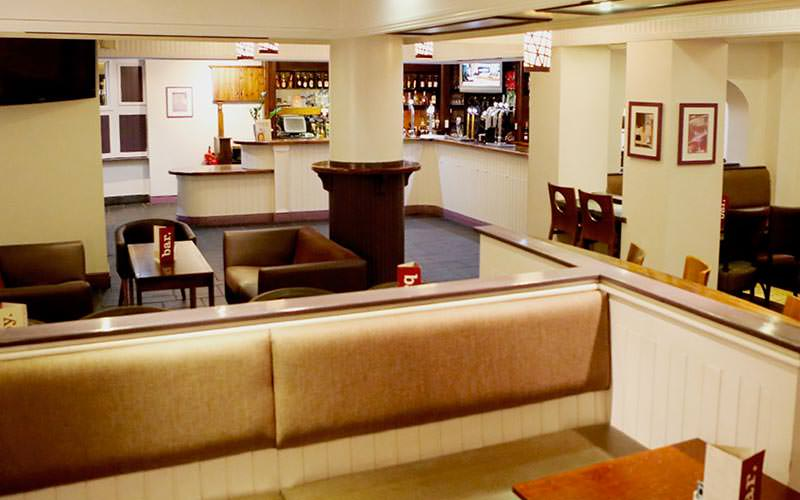 The bar and seating area with booth seating