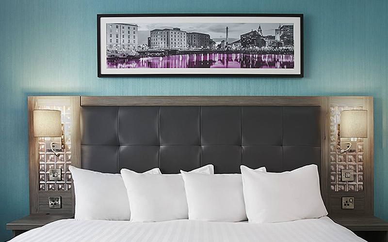 A white double bed in a hotel room, in front of a blue wall, with a picture above the bed