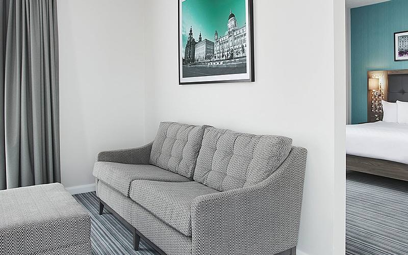 A grey sofa in front of a white wall, with a picture above, and a double bed in a blue room visible through an open door