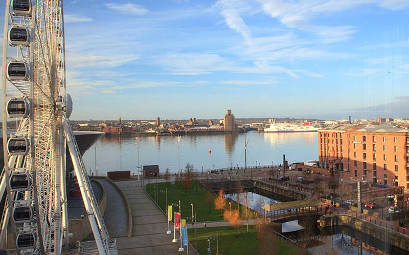 Liverpool's river with builsings and the big wheel in the foreground, during the day