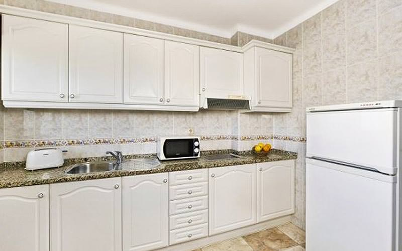 White kitchenette with appliances on top of the counters