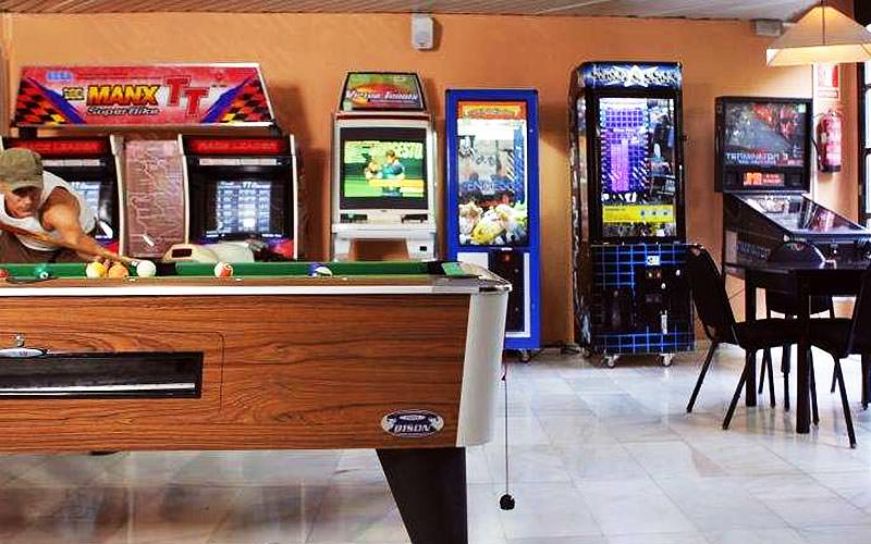 A games room with pool table, arcade games and pinball machine
