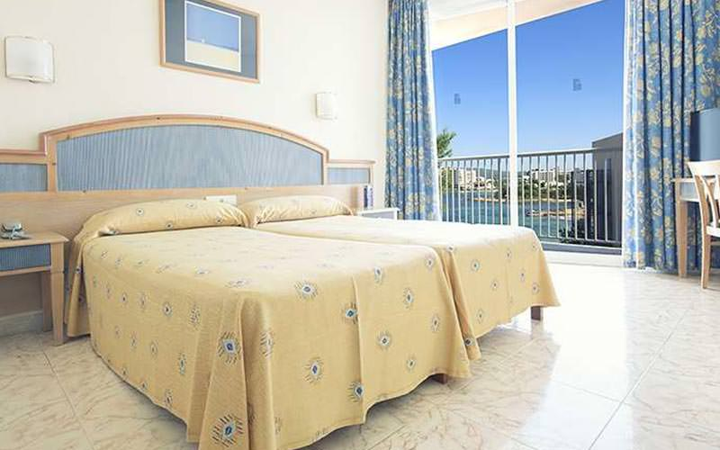 A spacious guest room with two twin beds and a balcony