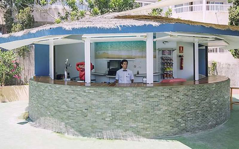 A round beach-style bar with a drinks taps and an awning