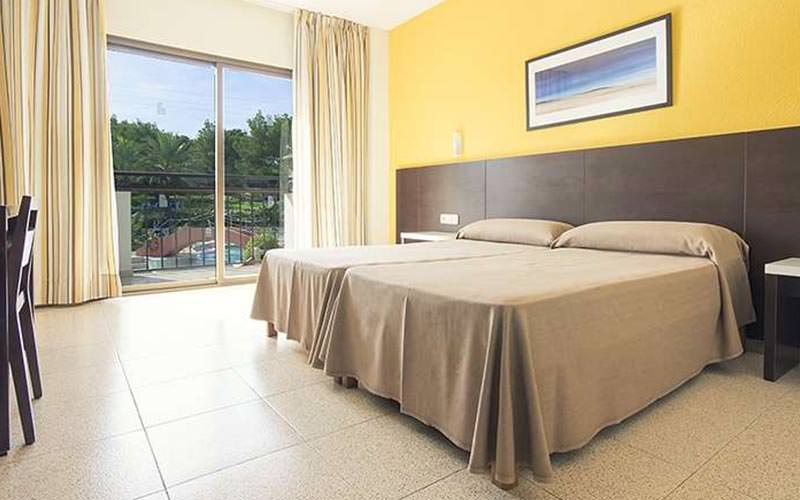A guest room at Azuline Mar Amantis with two twin beds and a yellow wall