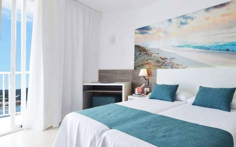 A light coloured guest room with two twin beds, a balcony and a large picture of a beach above the beds