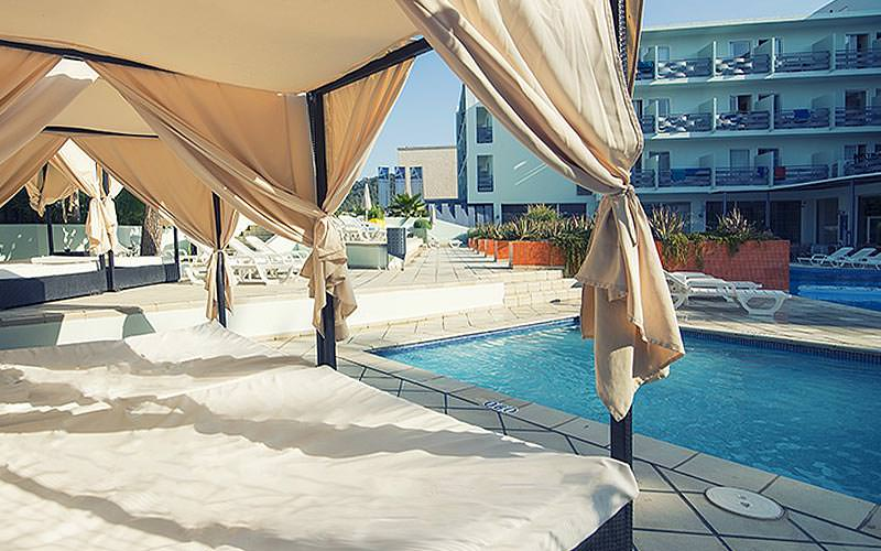 Four-poster cabana beds by an outdoor swimming pool