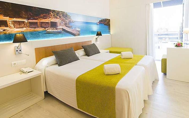 A guest room with two twin beds and a panoramic photograph print on the wall
