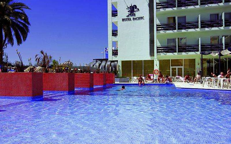 A view over the outdoor swimming pool and the exterior of the Hotel Pacific