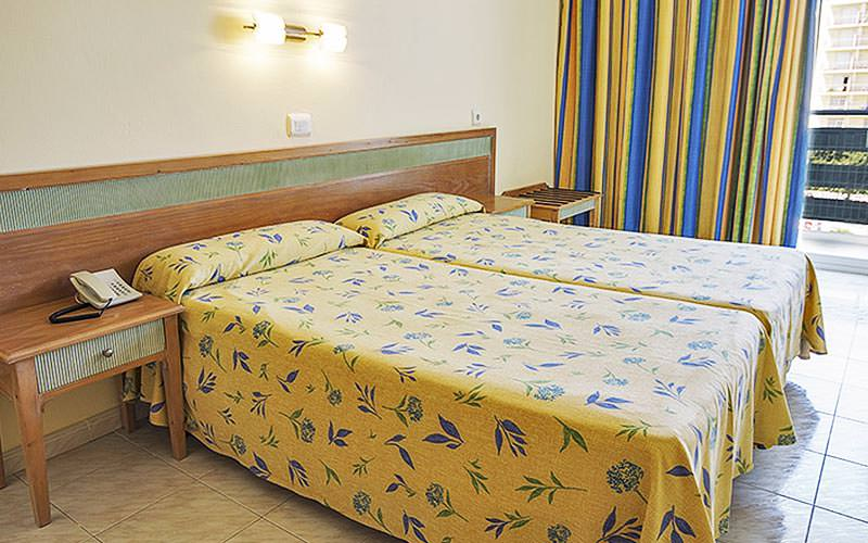 A guest room with two twin beds and yellow bedding and curtains