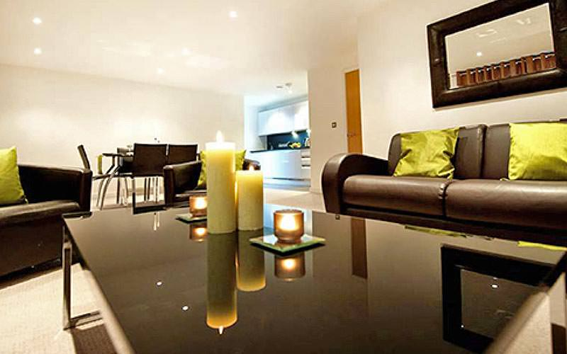 A black coffee table topped with lit candles, with leather sofas and a dining table in the background