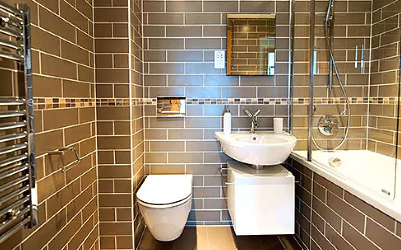 A grey tiled bathroom featuring a sink, toilet and bath