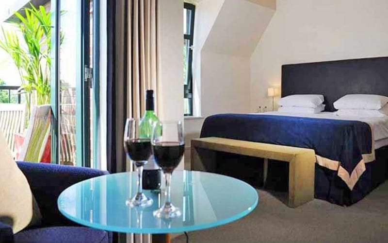 A double bed, topped with a blue throw, facing a stool at the end of the bed and a circular table topped with two glasses of red wine