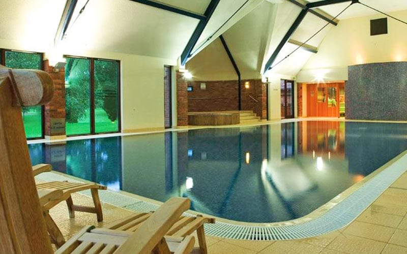 An indoor pool at Aldwark Manor Golf & Spa, with a wooden sun lounger in the foreground