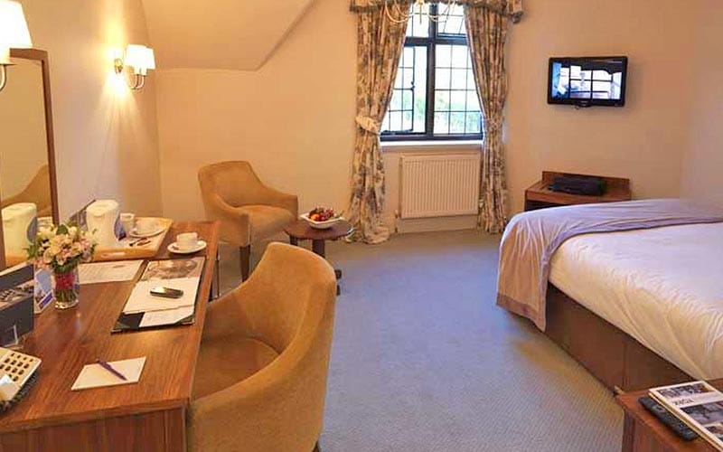 A double room at Aldwark Manor Golf & Spa, facing a desk and two comfy chairs