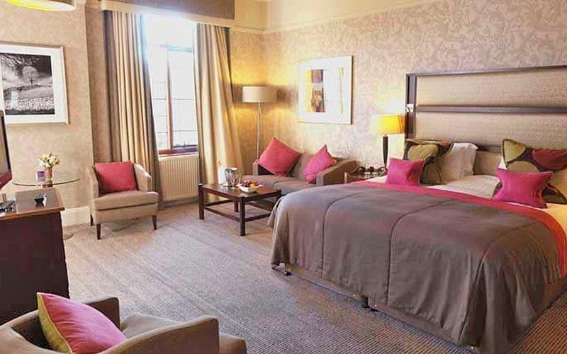A double room at Aldwark Manor Golf & Spa, with comfy chairs around the bed and a desk in the corner