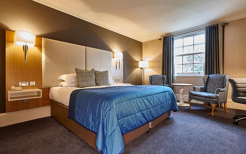 A double bed in a hotel room, topped with a blue throw, with two chairs in the back