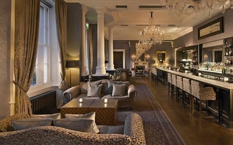 Sofas and tables in front of the bar at Oulton Hall