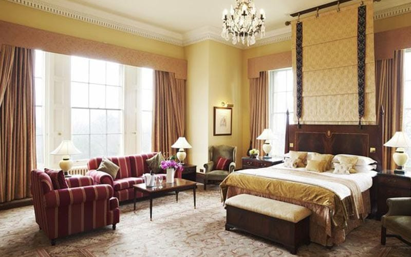 A double bed in a grand hotel room, with a sofa and chair around a coffee table in the corner