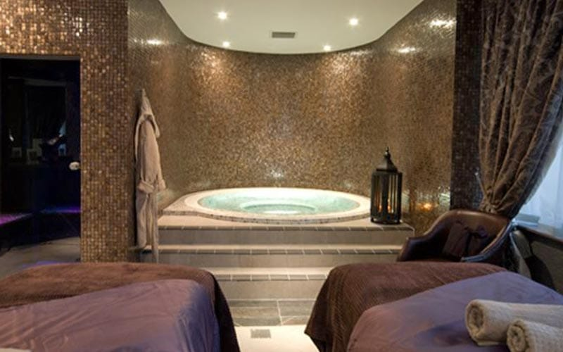 A luxury bath in a treatment room, with two massage beds in the foreground