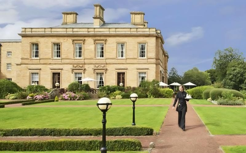 A woman walking in the grounds of Oulton Hall, with the building in the back