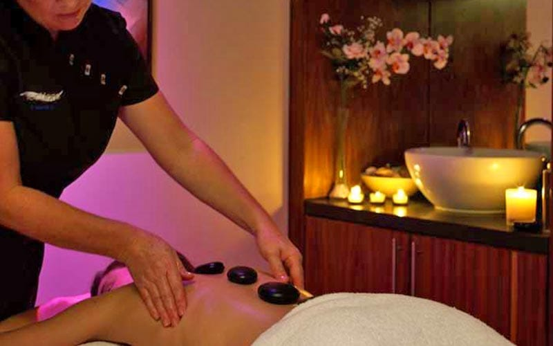 A beauty therapist giving a man a hot stone massage