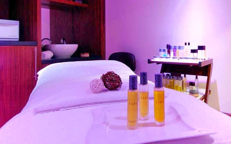 Three bottles of oil on a massage bed in a beauty treatment room
