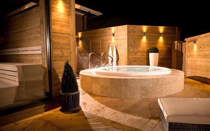 An outdoor Jacuzzi on a terrace at night