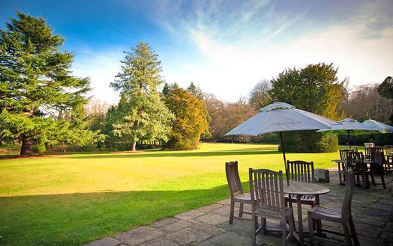The grounds of Mottram Hall, with tables and chairs on the outdoor terrace
