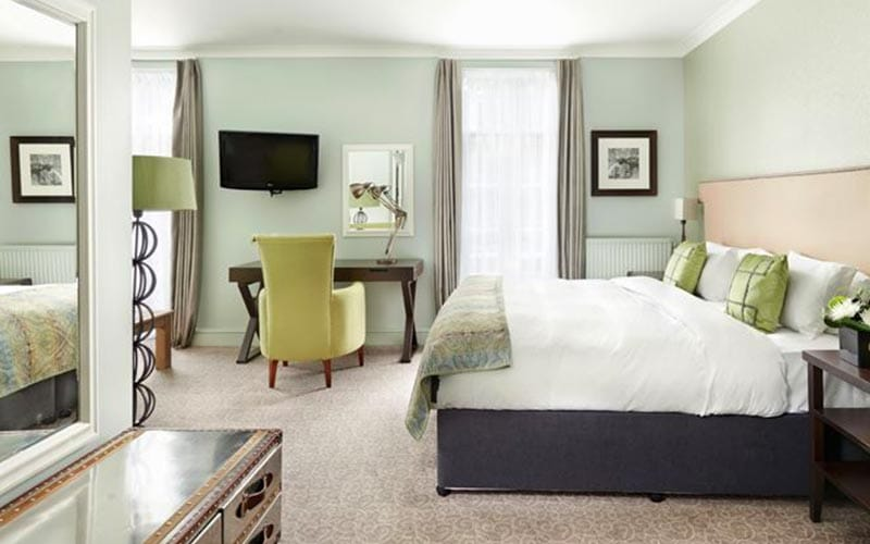A green hotel room at Mottram Hall, with a double bed, drawers and a desk