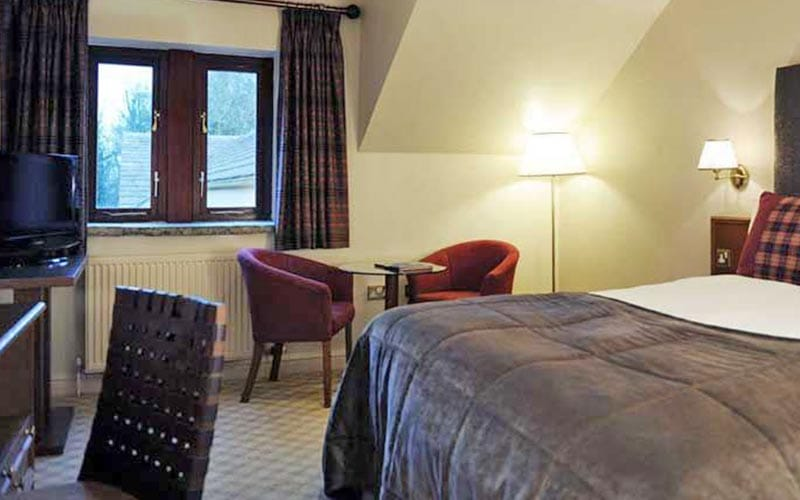 A comfortable double room in Tankersley Manor with a bed, three seats and a large window
