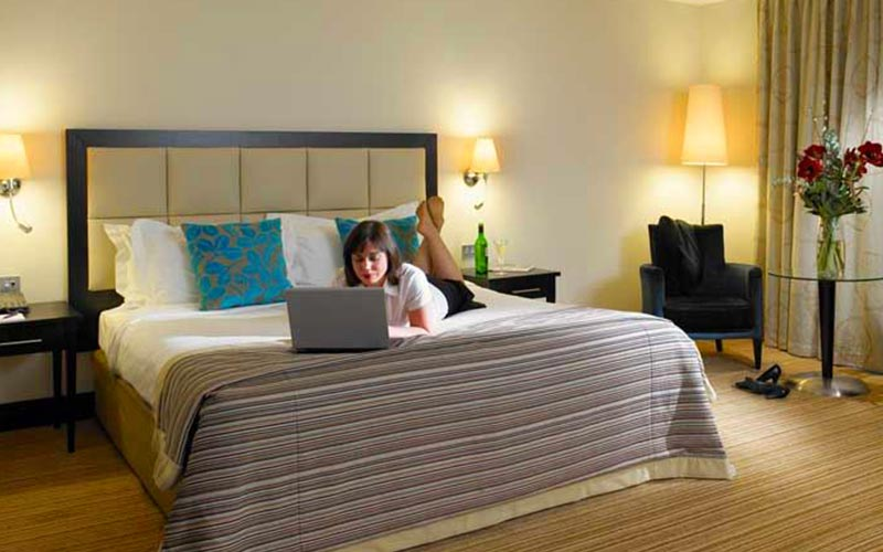 A woman lying on a bed with a laptop