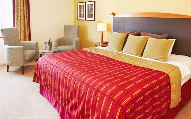 A double bed, topped with a red bedspread and gold cushions, in a hotel room at Belton Woods, with two chairs in the back