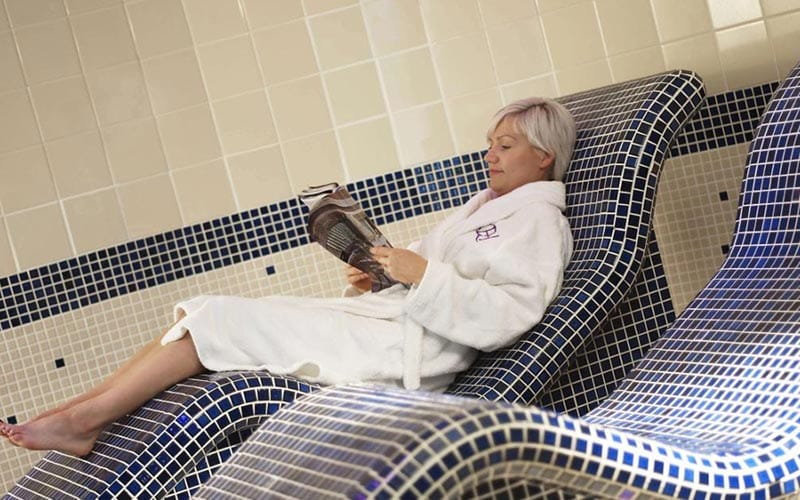 A woman reading a magazine on the tiled, blue and white lounger at Bridgewood Manor