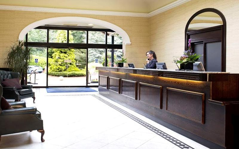 A woman on the phone at the reception desk at Bridgewood Manor