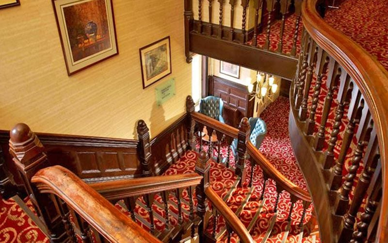 Winding wooden staircase at Bridgewood Manor