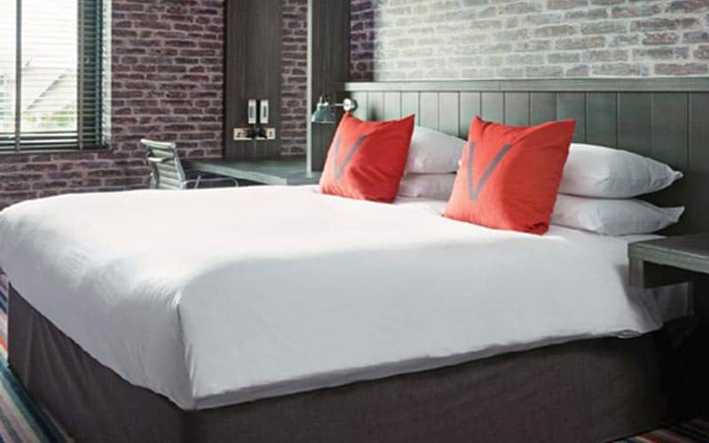 A double bed in a hotel room, topped with orange cushions with the letter V on